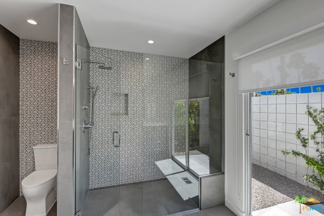A focused shot at this mid-century master bathroom's walk-in shower with a stylish wall along with gray tiles flooring.
