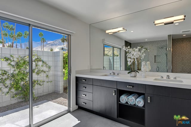 Mid-century master bathroom featuring a sliding glass door leading straight to the outdoor area. The bathroom also has a walk-in shower room and a sink counter featuring a double sink.