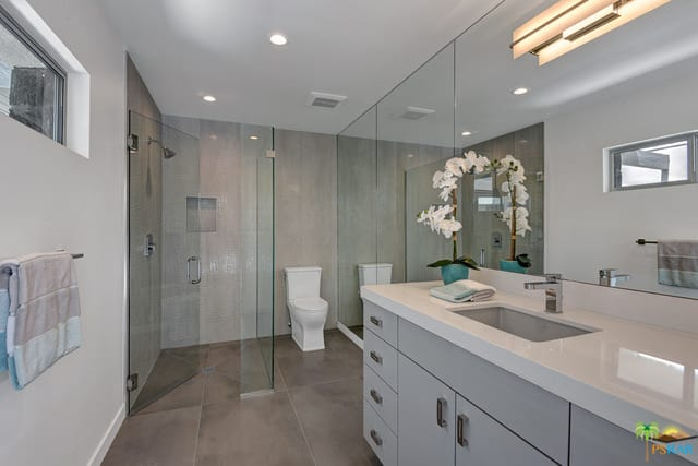 A narrow mid-century style primary bathroom featuring a toilet area and a walk-in shower, along with a gray cabinetry and white sink counter.