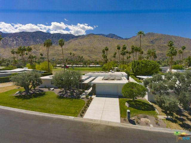 Aerial view of the entire property of the white mid-century home on Indian Canyons Golf Course with spectacular mountain views.