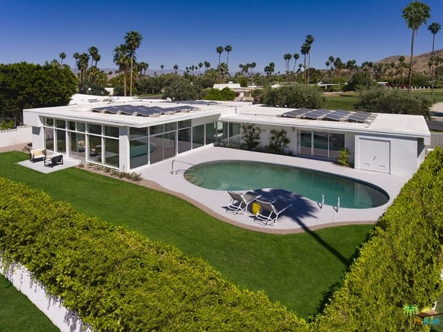 The spacious backyard with a kidney-shaped pool, a concrete patio, and an expansive green lawn is tucked away in a privacy hedge.