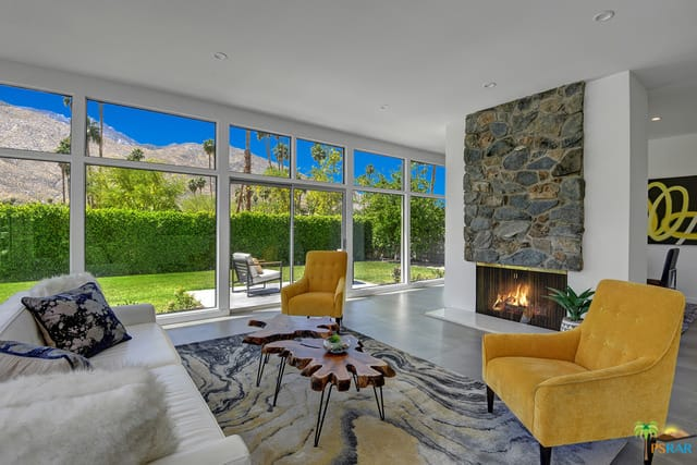 Mid-century modern living room features yellow tufted chairs and a white couch facing the fireplace that's accented with a stone panel. It has concrete flooring and full height windows with a scenic view.