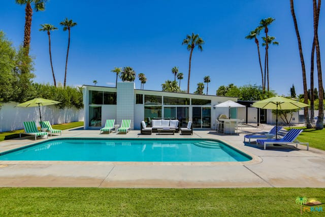 A small mid-century house with a spacious outdoor area featuring a swimming pool, a patio area, multiple sitting lounges and a well-maintained lawn area.