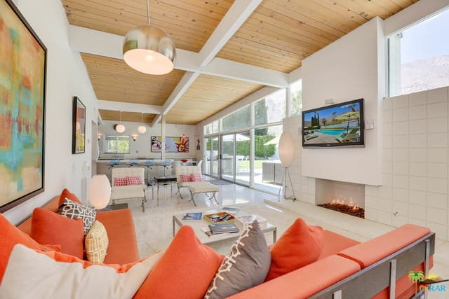 The interior features white walls and a wooden ceiling with white beams. There's a fireplace near the living space and it has a widescreen TV on the wall.