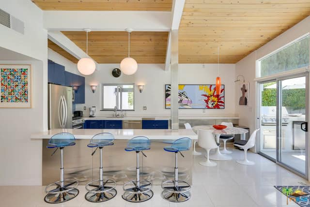 Decorative dine-in kitchen in polished white and blue accents, breakfast island, stainless steel appliances, and a playful combination of pendant and wall mounted lights.