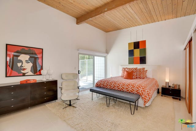Mid-century modern primary bedroom featuring white floors topped by an area rug along with white walls with wall decors.