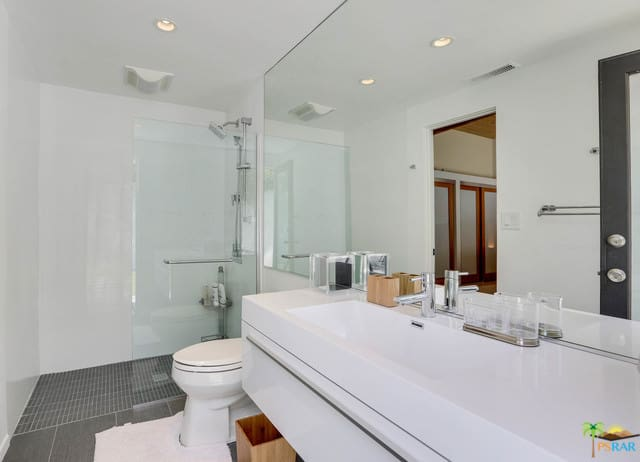 A narrow mid-century style master bathroom featuring white walls and a white floating vanity sink together with a small shower area.
