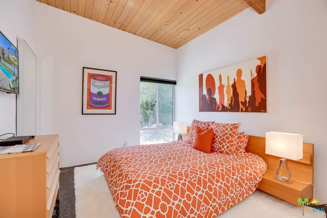 Small mid-century modern master bedroom with a nice bed with two table lamps and interesting wall decors.