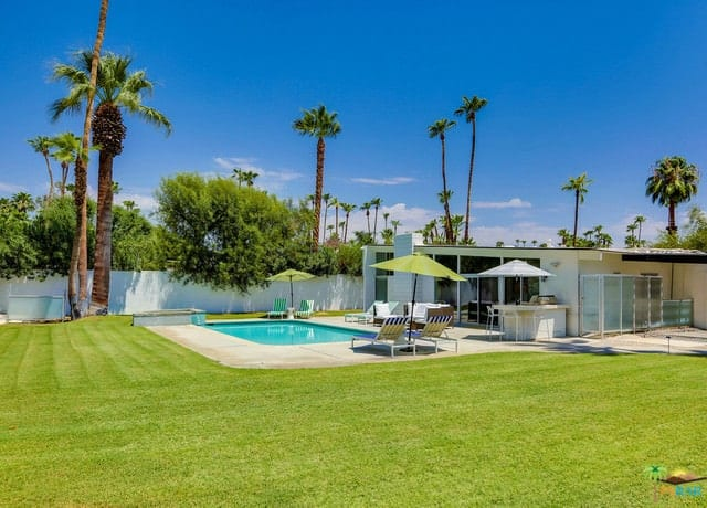 The private property has a spacious backyard with a square pool, an outdoor kitchen, an expansive lawn, and towering palm trees.