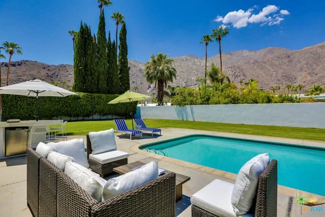 The large backyard includes a pool, an outdoor kitchen, a concrete patio, and a lawn hidden behind the privacy walls while enjoying the breathtaking mountain views.