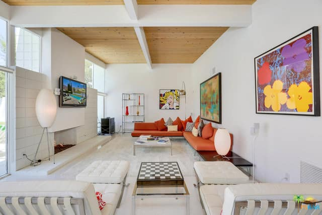 White mid-century living room accented with lovely wall arts and a coral sofa accompanied by metal tables and white tufted lounge chairs.