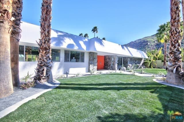 A Mid-century style house with a white exterior. It also boasts manicured lawns and tropical trees set on its backyard.