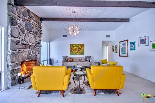 Mid-century modern living room accented with yellow armchairs that face the coffee table and gray tufted sofa illuminated by a gorgeous chandelier.