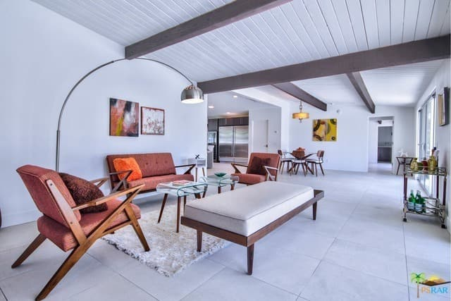 White living room showcases tiled flooring and shiplap ceiling lined with wood beams. It has a glass top coffee table surrounded by coral tufted seats and gray cushioned bench.