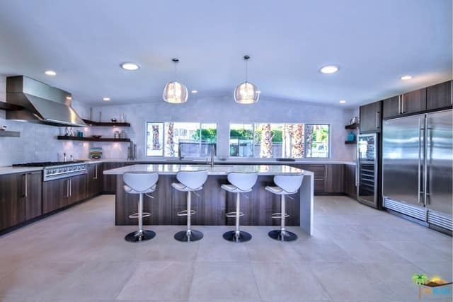 Spacious U-kitchen with a huge stainless steel refrigerator, breakfast island, wooden cabinets, floating shelves, and pendant lights.