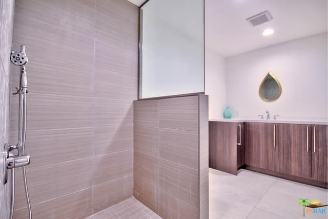 A classy primary bathroom in mid-century style featuring a shower area covered in brown tiles walls and floors.