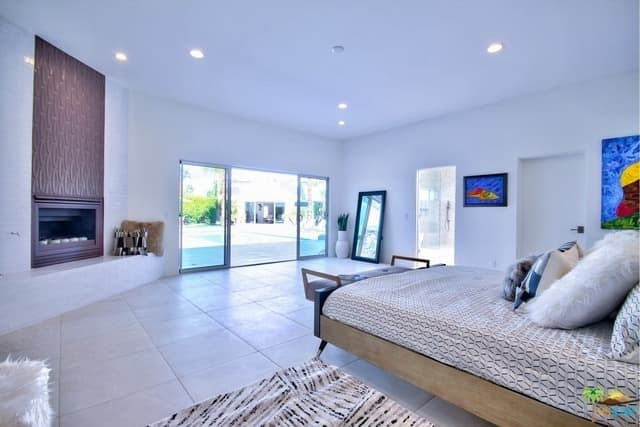 This primary bedroom in a mid-century modern style has white walls and ceiling lighted by recessed lights. It also features a doorway leading to the home's backyard. Additionally, it has a fireplace, keeping the room warm.