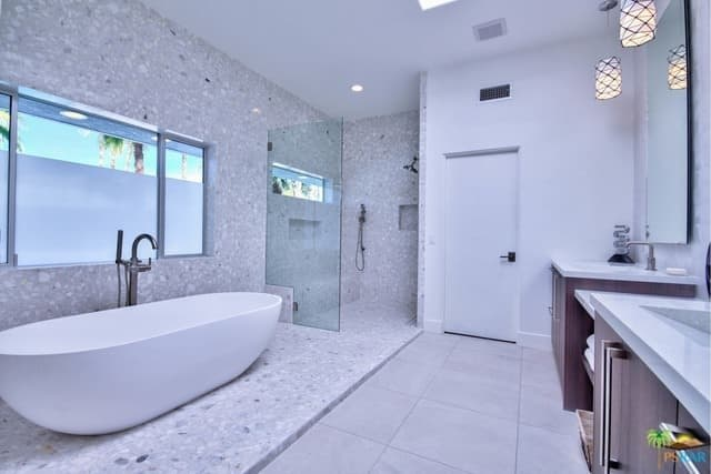 Spacious primary bathroom in mid-century style featuring a large freestanding tub and a walk-in shower room.