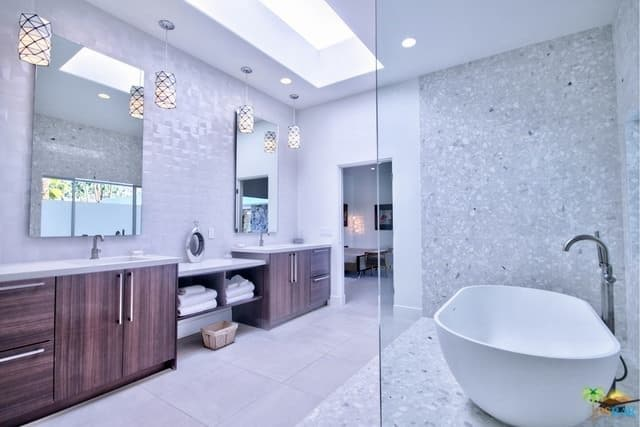 A mid-century style primary bathroom featuring two sink counters with sinks lighted by pendant lights and a large skylight.