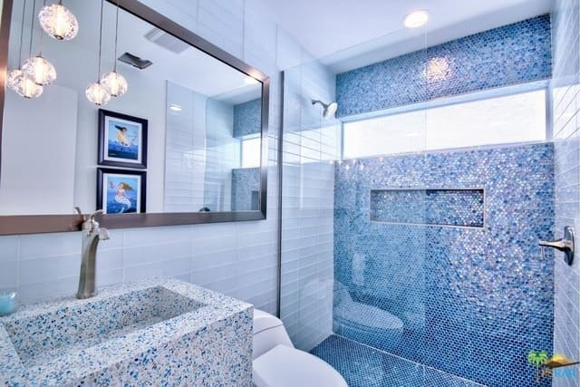 A small mid-century primary bathroom featuring a very stylish sink along with a very attractive blue walled shower room.