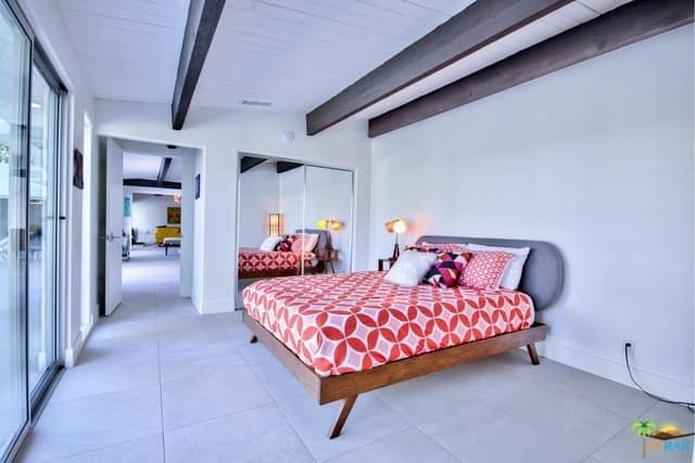 Mid-century modern primary bedroom featuring white tiles flooring and walls, along with a white ceiling with exposed beams.