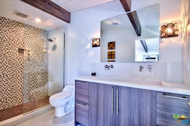 Another look at this primary bathroom in mid-century style featuring a stylish walk-in shower and a double sink lighted by wall lights.