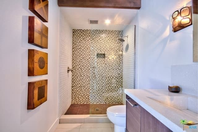 A narrow mid-century primary bathroom featuring a very stylish shower area.