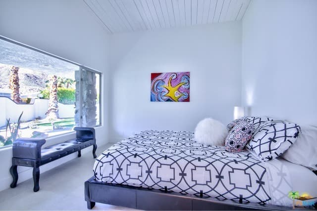 White mid-century modern primary bedroom featuring a large bed with a wide glass window in front, overlooking the property's outdoor area.
