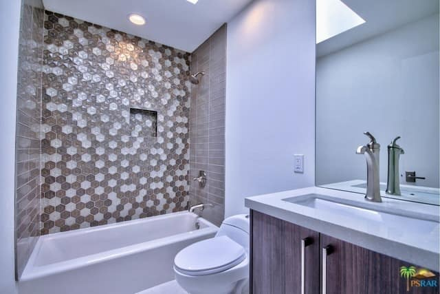 Mid-century master bathroom featuring a stylish drop-in tub lighted by a skylight.