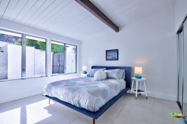 This mid-century modern primary bedroom offers a bed with a blue frame with two side tables topped by a pair of table lamps.