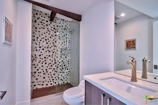 This mid-century style primary bathroom boasts a stylish shower area and a sink counter with brown cabinetry.