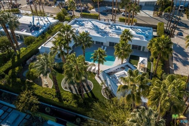 Aerial view of a luxurious mid-century estate with a sweeping backyard of towering palm trees and manicured grounds hemmed in by a privacy hedge.