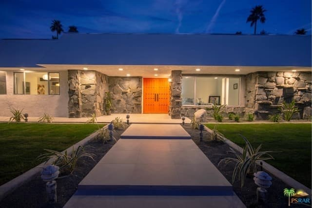 The concrete walkway leading to the home's front door is flanked by the front yard garden with minimalist landscaping.