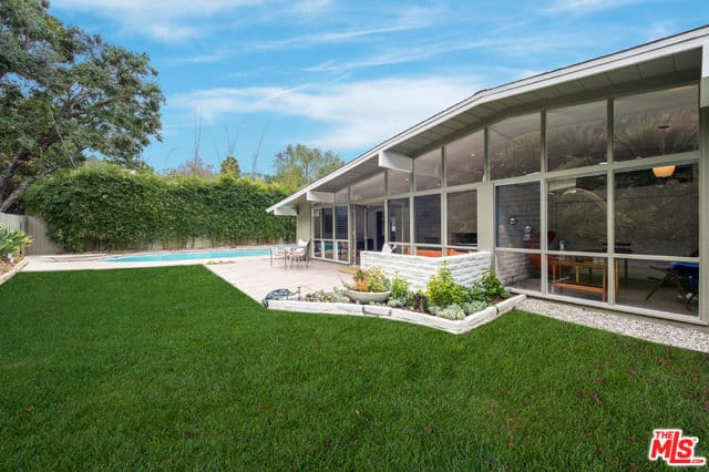 A mid-century house with a healthy garden and a pool area. Its glass walls and windows give the home a light-filled interior.
