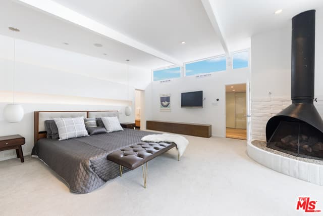 This mid-century modern primary bedroom boasts a large bed and a fireplace surrounded by white walls and white carpet flooring.