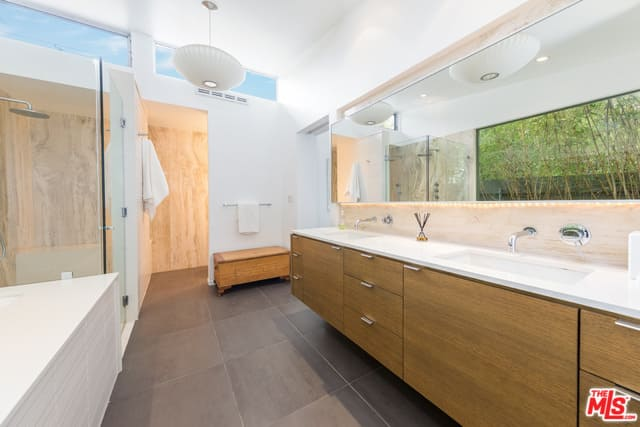 This mid0century primary bathroom features a bright shade of white along with gray tiles flooring.