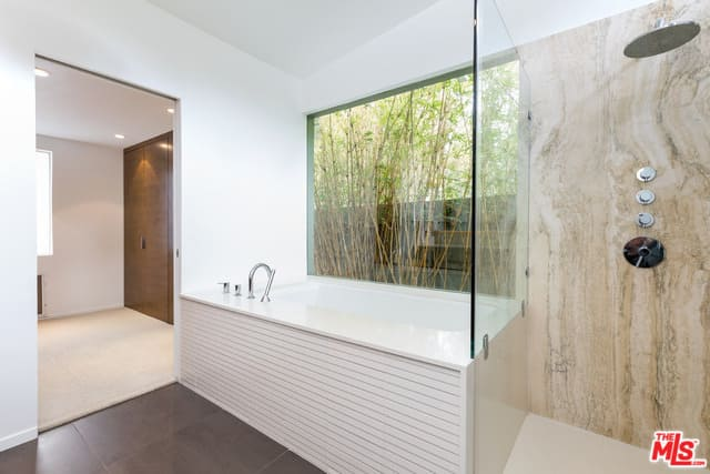 A close up look at this mid-century style primary bathroom's deep soaking tub by the glass window, together with the walk-in shower room.