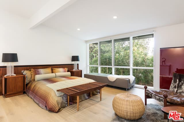 Mid-century modern primary bedroom featuring white walls and glass windows. It also offers a stylish bed with two table lamps on the pair of side tables.