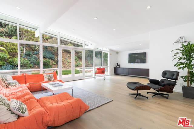 Spacious mid-century living room with smooth hardwood flooring and full height glazing overlooking the serene outdoor filled with abundant greenery.