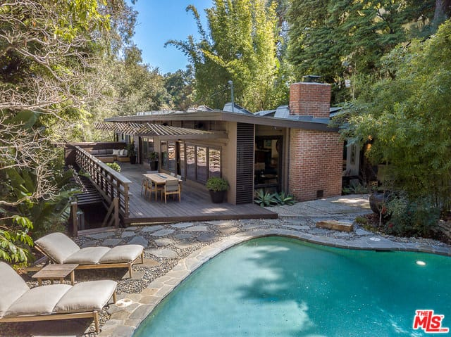A mid-century house surrounded by natural woods. It has a deck providing a breathtaking view of the nature and a nice swimming pool on the side.