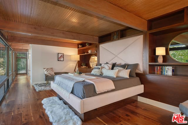 Mid-century modern primary bedroom featuring hardwood floors and a wooden ceiling with exposed beams, along with glass windows overlooking the outdoor views.