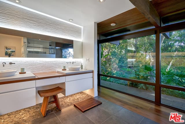 Mid-century primary bathroom featuring two vessel sinks on a floating vanity along with glass walls overlooking the peaceful outdoor surroundings.
