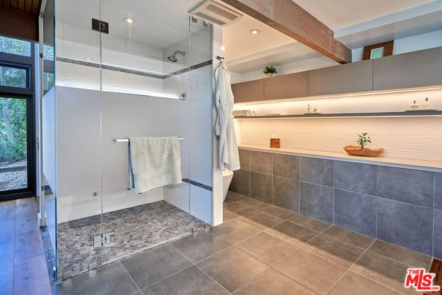 This primary bathroom in mid-century style features gray walls and a walk-in shower room.