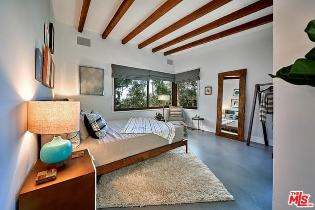Small mid-century modern primary bedroom with gray floors and white walls, along with a ceiling with beams.