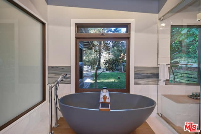 A close up look at this mid-century primary bathroom's stylish gray freestanding tub.