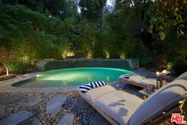 A combination of stone slab walkways and pebbled stones create a rustic touch to the beach-entry pool while the underwater pool lighting brings attention to the privacy wall of foliage that creates a tropical feel.