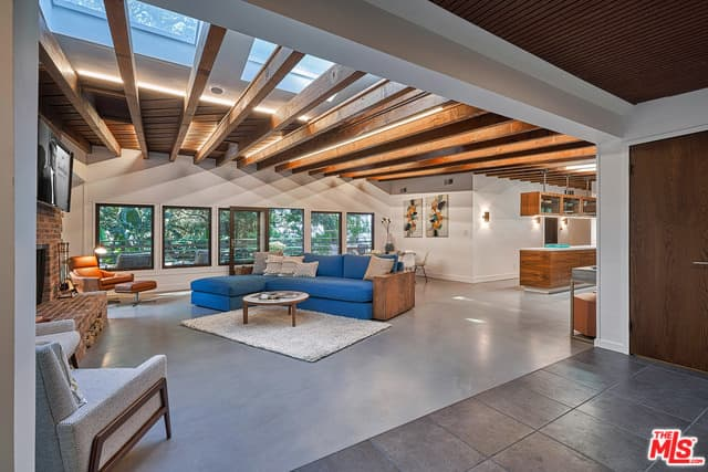 Natural light streams in through the glass paneled windows and skylights in this mid-century modern living room accented with an L-shaped sofa that's paired with a round coffee table on a gray area rug.