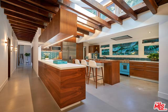 Spacious Midcentury Modern kitchen with wooden beam ceiling accents, wooden breakfast island, stainless steel appliances, and huge windows.