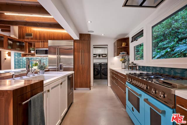 Wide residential kitchen with wooden cabinets, recessed ceiling lights, stainless steel appliances, and a kitchen island.