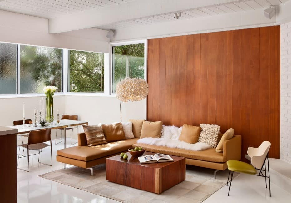 Fluffy brown pillows and white faux fur blanket lay on the L-shaped sofa in this living room showcasing a sleek coffee table illuminated by a gorgeous chandelier that hung from the white wood beam ceiling.